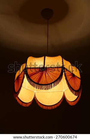 A textile chandelier shining by yellow light - stock photo