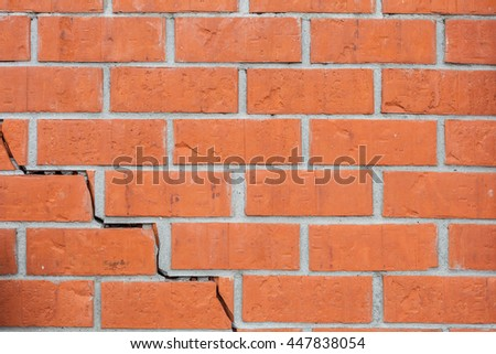 A texture deformed  brick wall with a crack. Destroyed stone stack. - stock photo