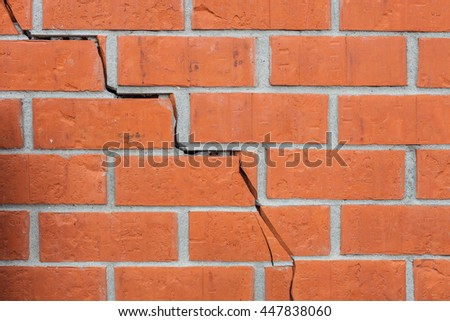 A texture deformed brick wall with a crack. Destroyed stone stack.