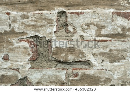 A texture of brick wall covered with old plaster