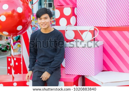 A Thai boy sitting on the stack of christmas box in Hua Hin Thailand, December 9, 2017