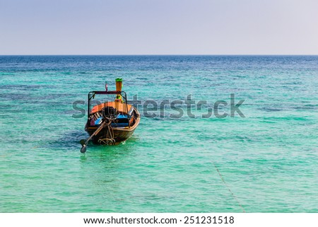 a thai traditional long tail boat in a tropical island with azure vibrant sea - stock photo