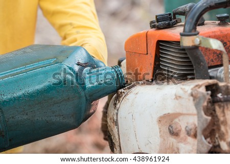 A Thai worker filling oil to engine of chainsaw - stock photo