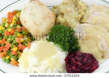 A Thanksgiving meal, with sliced turkey, dressing, mashed potatoes with gravy, mixed vegetables, cranberry relish and a roll, closeup - stock photo
