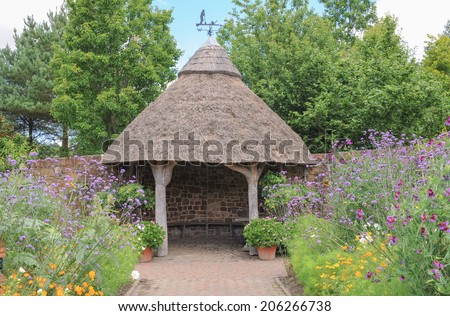 A thatched summerhouse in a traditional English Country Fruit and Vegetable Garden at Rosemoor, close to Torrington, Devon, England, UK - stock photo