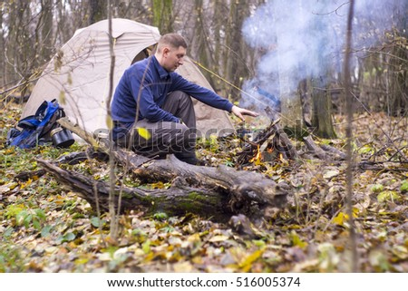 a The guy sitting in the woods near the tent