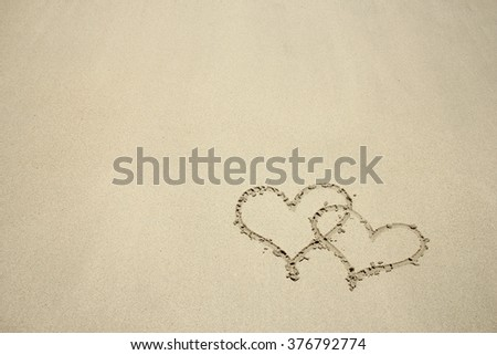 a the inscription two hearts on the sand by the sea - stock photo