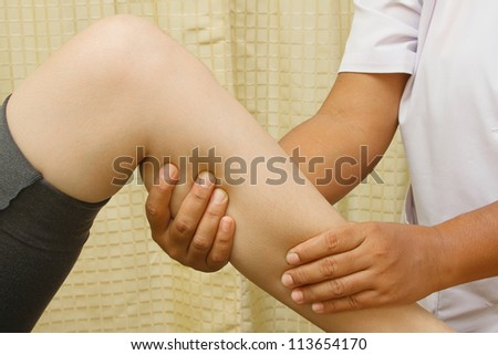 a therapist giving knee and leg massage release muscle pain - stock photo