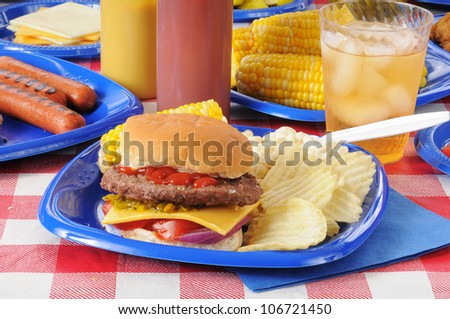 A thick cheeseburger with potato chips on a picnic table - stock photo
