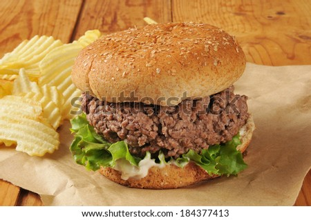 A thick hamburger on brown paper with potato chips