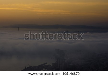 A thick layer of fog across the town and habour of Gibraltar - stock photo