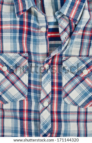 A thick man's shirt with checked blue,red and white pattern - stock photo