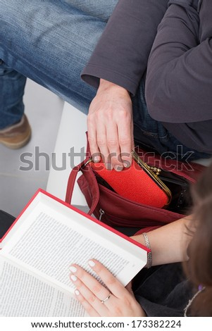 A thief taking a purse out of a woman's reading a book bag - stock photo