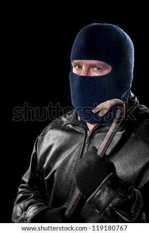 A thief wearing a ski mask to hide his identity holds a crowbar and prepares to commit a crime.