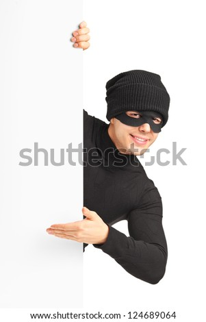A thief with robbery mask gesturing on a blank panel isolated on white background - stock photo