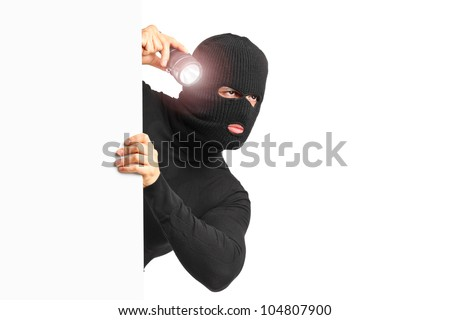 A thief with robbery mask holding a flashlight behind a white panel isolated on white background - stock photo
