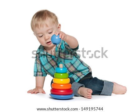 A thoughtful baby boy is playing with toys on the white - stock photo