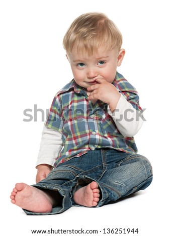 A thoughtful baby boy is sitting on the white background - stock photo
