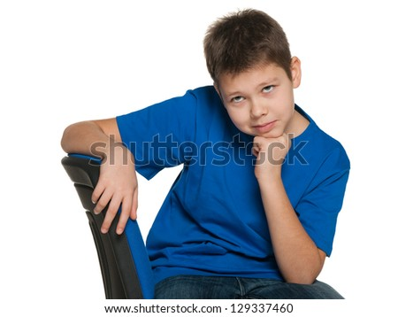 A thoughtful boy is sitting on the chair on the white background - stock photo