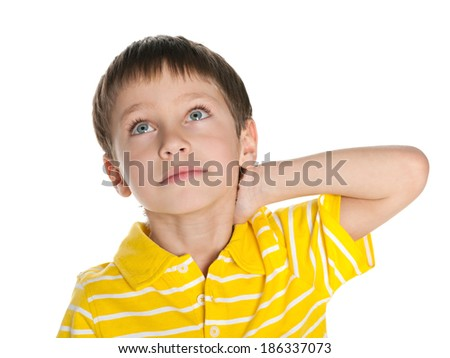 A thoughtful little boy looks up on the white background