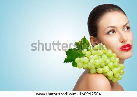 A thoughtful sexy lady with a bunch of healthy green grapes on her shoulder looking aside. - stock photo