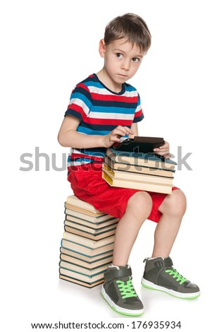 A thoughtful young boy is sitting on the pile of books and holding a new gadget