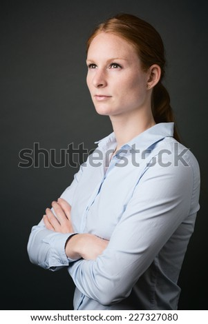 A thoughtful young visionary business leader poses with folded arms before a plain dark background.
