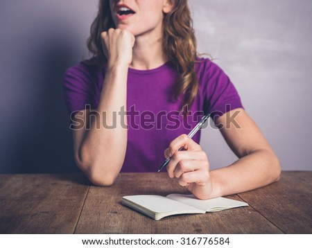 A thoughtful young woman is writing in a notepad at a table - stock photo