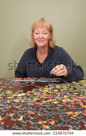 A thousand piece jigsaw puzzle put together by a blonde haired white woman - stock photo