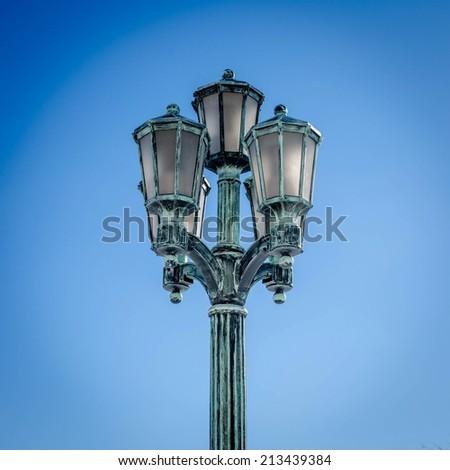 A three-light streetlight against a clear blue sky. - stock photo