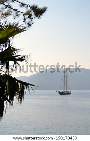 A three-masted sailing vessel in a calm bay in the early morning - stock photo