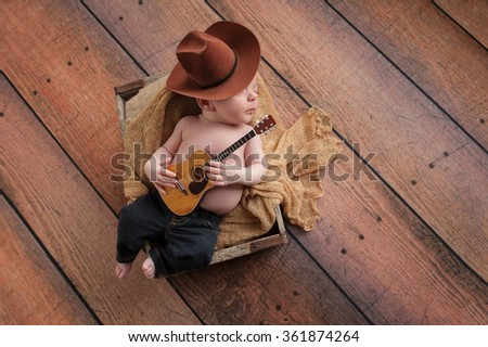 A three week old baby boy wearing a cowboy hat and jeans and playing a tiny acoustic guitar. He is lying in a wooden crate lined with burlap. Shot in the studio on a rustic, wood background. - stock photo