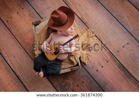 A three week old baby boy wearing a cowboy hat and jeans and playing a tiny acoustic guitar. His lips are pursed, as if whistling. He is lying in a wooden crate on a rustic, wood background. - stock photo