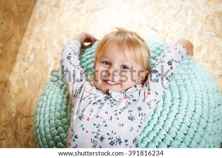 A three year old girl posing like a model in a pink room, in white blouse and pink pants with makeup red lips and a hairstyle making funny face expression - stock photo