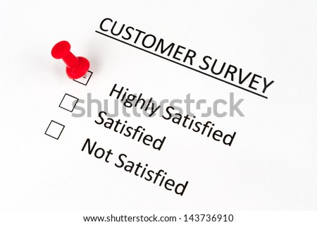 A thumbtack pinned on customer survey paper with options of highly satisfied, satisfied and not satisfied - stock photo