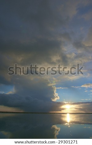a thunder storm with dark rain clouds in summer over the ocean with a beautiful reflection