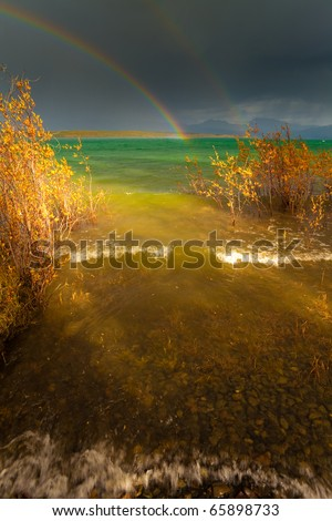 A Thundershower producing a rainbow over the gree-blue waters of pristine Lake Laberge, Yukon Territory, Canada. - stock photo