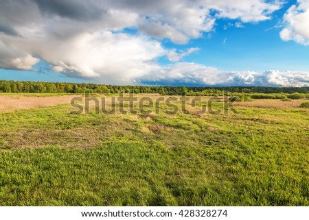 A thunderstorm over the green field - stock photo