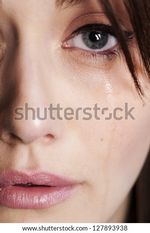 A tight close up of half of a womans face with tear running down cheek from crying.