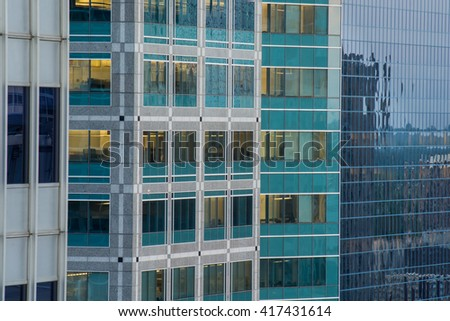 A tight shot of the side of three downtown office buildings at dusk. - stock photo