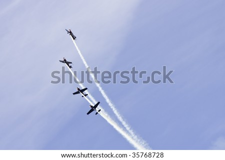 A tightly synchronized aerobatics display team perform a stunt.  All markings removed from aeroplanes.