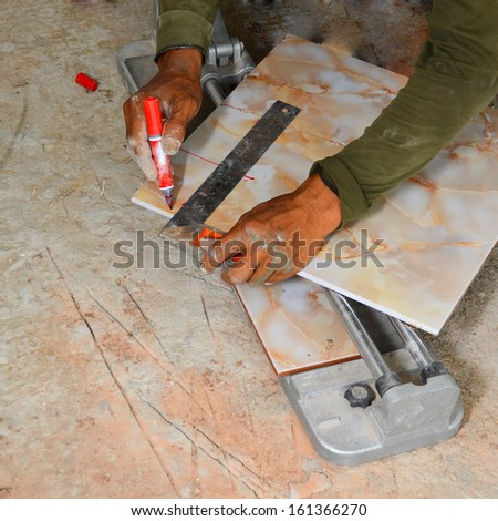 A tiler cutting tiles. - stock photo
