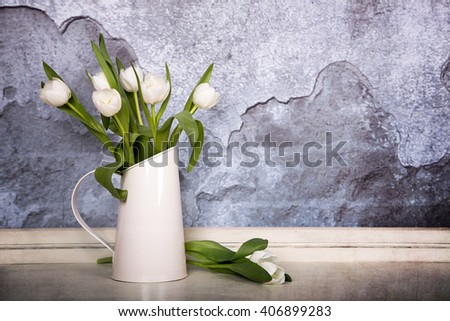 A tin jug filled with white tulips, over old plaster wall with grunge texture. Space for text
