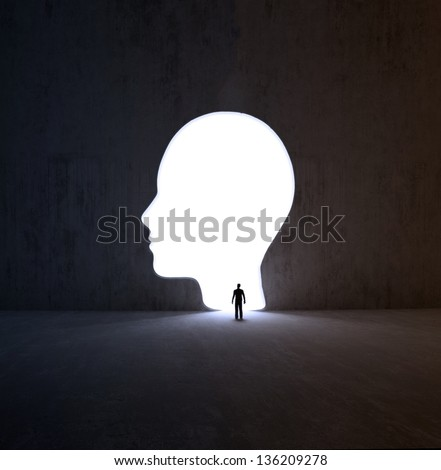 A tiny man walking into a head-shaped opening in a wall - stock photo