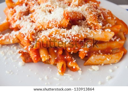A tipicall italian dish of pasta: penne with tomato sauce and parmisan cheese - stock photo