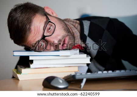 A tired nerd falling asleep on a bunch of books - stock photo