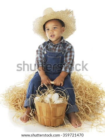 "A tired preschool ""farmer"" relaxing on a hay stack while holding onto his basketful of eggs.  On a white background. - stock photo"