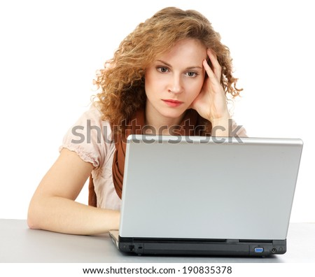 A tired woman in front of a laptop , isolated on white background - stock photo