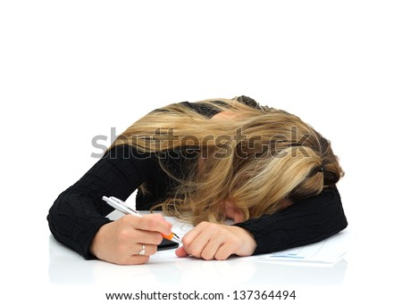 A tired woman sleeping on the desk at work - stock photo