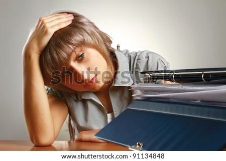 A tired young woman sitting at the desk, having a lot of paperwork to do - stock photo